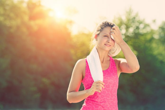 female runner wiping sweat after a running workout