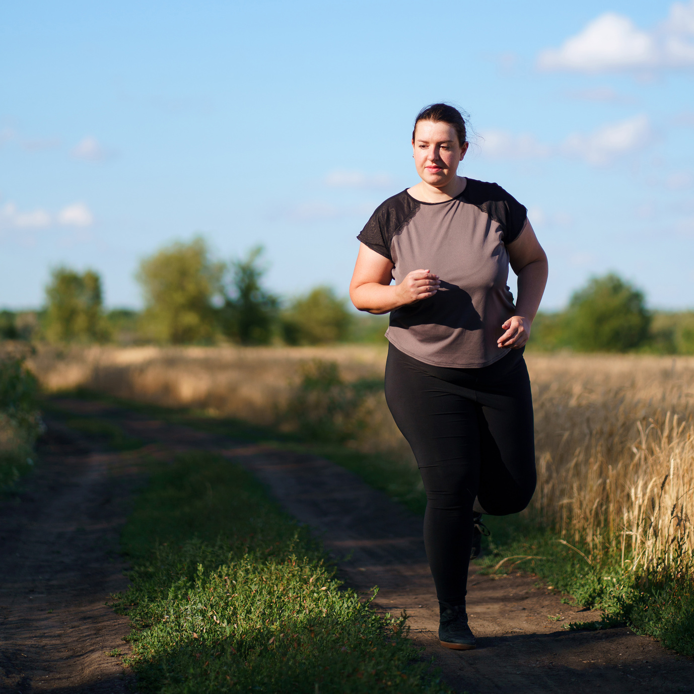 Overweight woman running in countryside